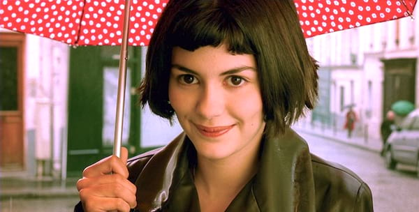 Scene from French film, Amelie where the titular character is softly smiling under a red and white polka dot umbrella in Paris
