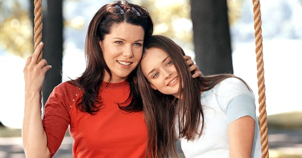 Lorelai and Rory sitting on a swing together in a scene from 'Gilmore Girls'