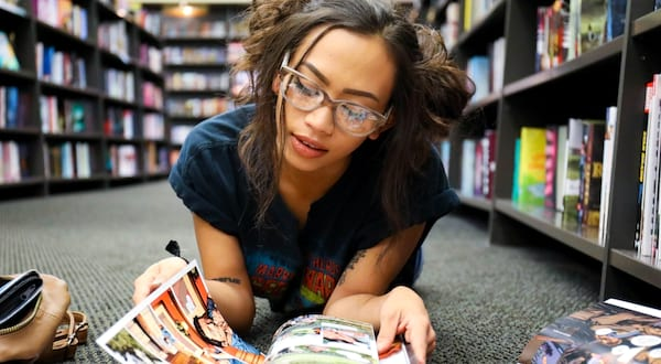 horror comics for halloween, a black woman with her hair up lies on the floor reading a comic, books