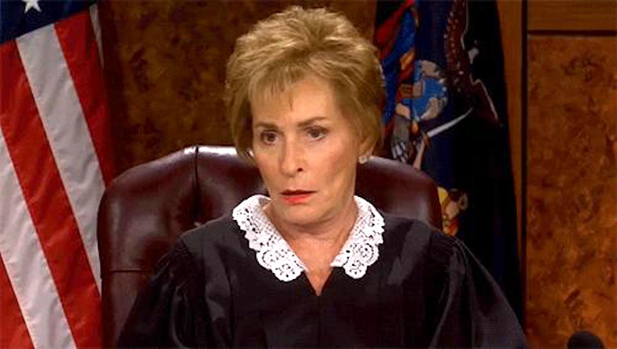 Judge Judy in her robe, with an American flag behind her at her bench