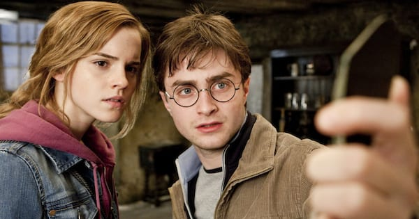 Hermione and Harry looking at a broken shard of something in 'Harry Potter and the Deathly Hallows—Part 2'