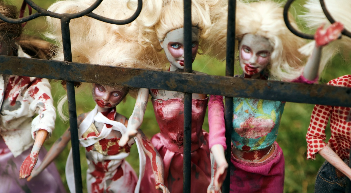 zombie books, a group of zombie barbies by a fence, books