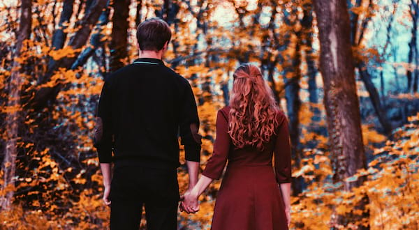 autumn romance novels, a straight white couple facing away from the camera surrounded by falling orange leaves, books