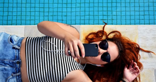 woman laying down by pool holding iphone cell phone above face