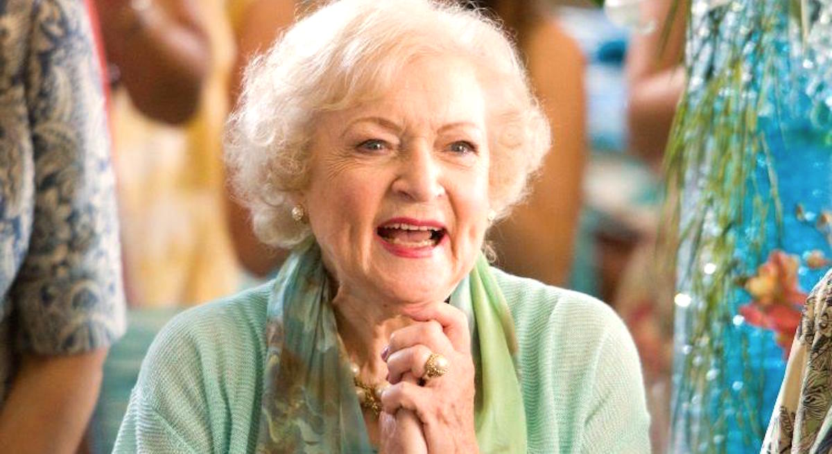 Betty White holding her hands in excitement while wearing a light green shirt and green scarf