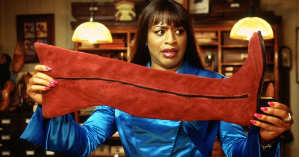 Chiwetel Ejiofor dressed as Lola holding up a burgundy shoe in 'Kinky Boots'