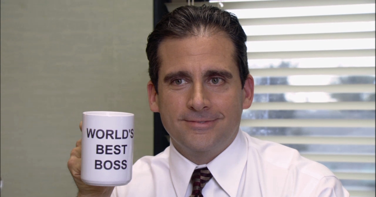 Michael Scott holding up the \World's Best Boss\ mug he bought himself on 'The Office'