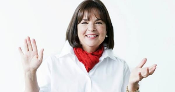 Ina Garten in a white shirt, smiling with her hands up wearing a red scarf