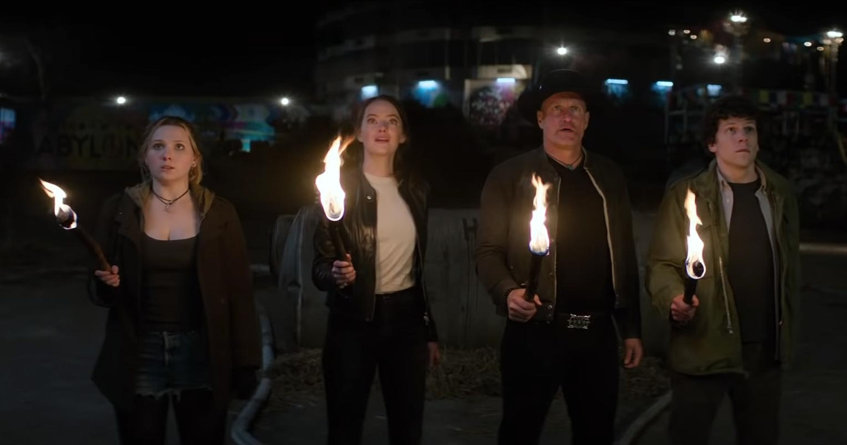 The cast of Zombieland: Double Tap holding lit torches while staring up at something off-screen
