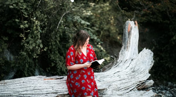fluffy romance novels, photo of a white woman in a red dress reading a book, books