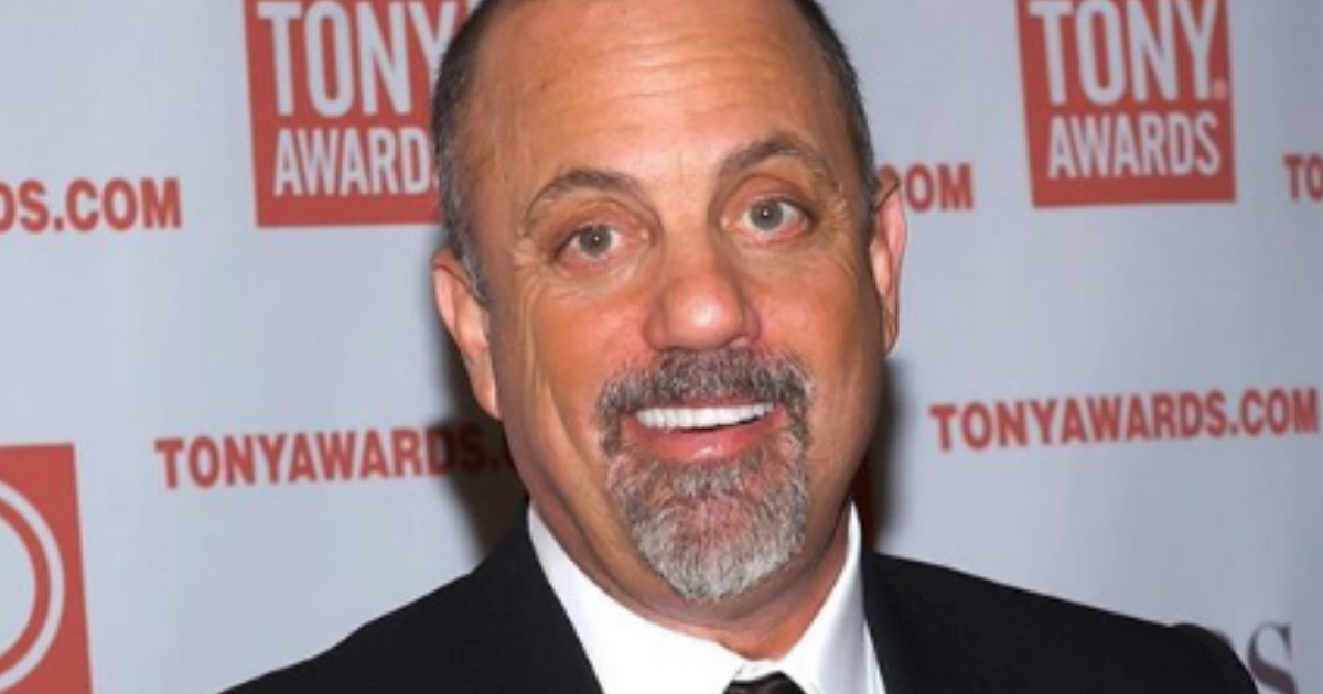 Billy Joel smiling in a suit
