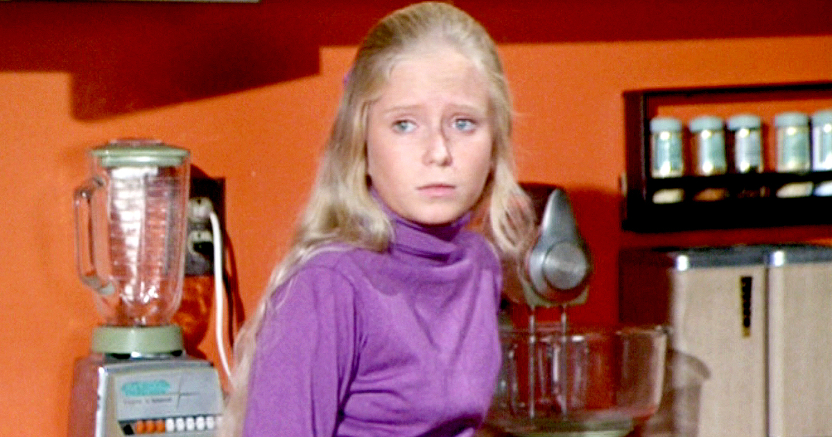 Jan wearing a purple shirt and looking upset at something off-camera in 'The Brady Bunch'