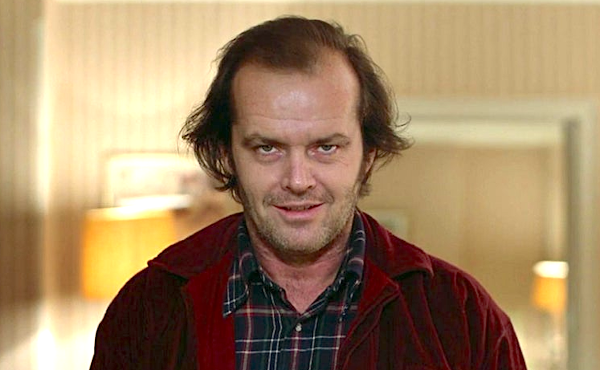 Jack Nicholson as Jack Torrance in 'The Shining' wearing a maroon jacket, plaid button down, looking possessed