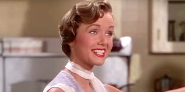 Debbie Reynolds singing and smiling with a white scarf around her neck in a scene from 'Singing in the Rain'