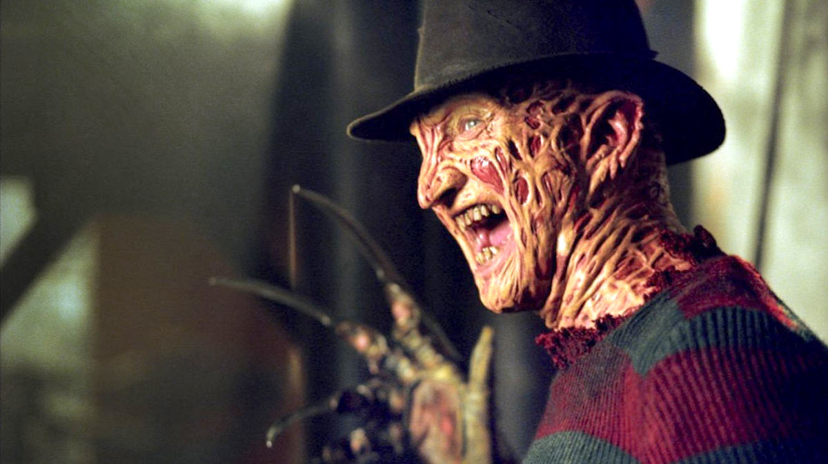 Freddy Krueger laughing wearing his signature hat and red and black striped sweater with his sharp hand in frame