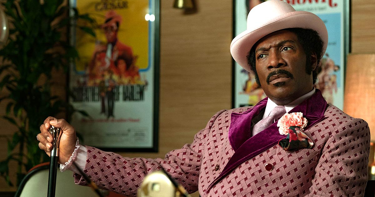Eddie Murphy as Dolemite staring blankly at a movie producer in 'Dolemite Is My Name' on Netflix