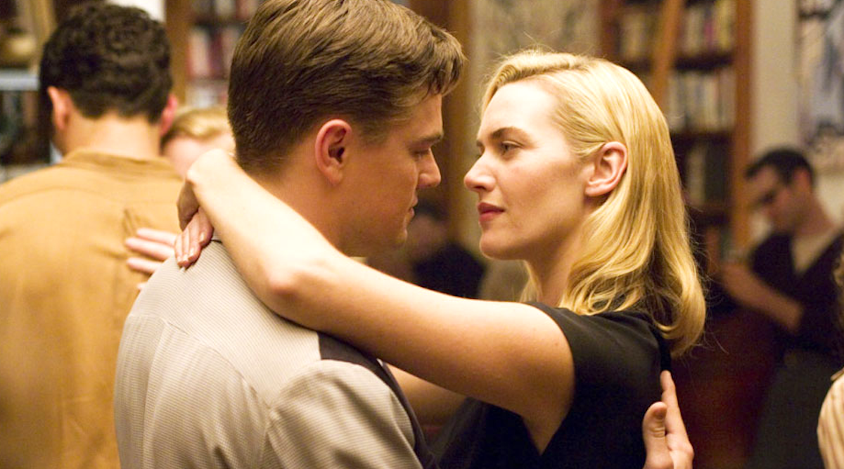 Leonardio DiCaprio and Kate Winslet smiling dancing together in a scene from 'Revolutionary Road'