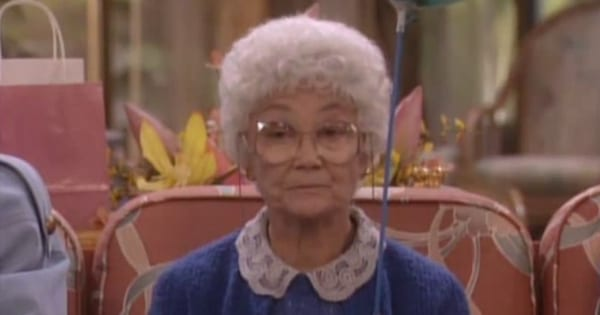 Sophia sitting on the couch holding a balloon with a sullen expression on her face in 'The Golden Girls'