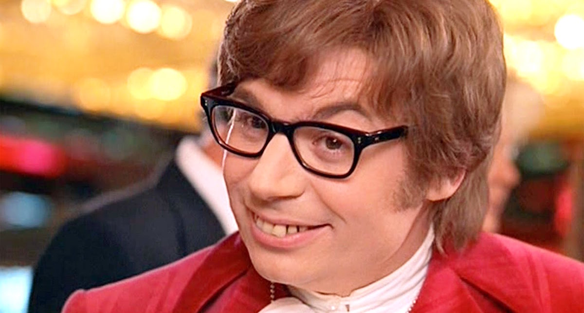 Mike Meyers as Austin Powers smiling with terrible teeth and in a velvet red suit