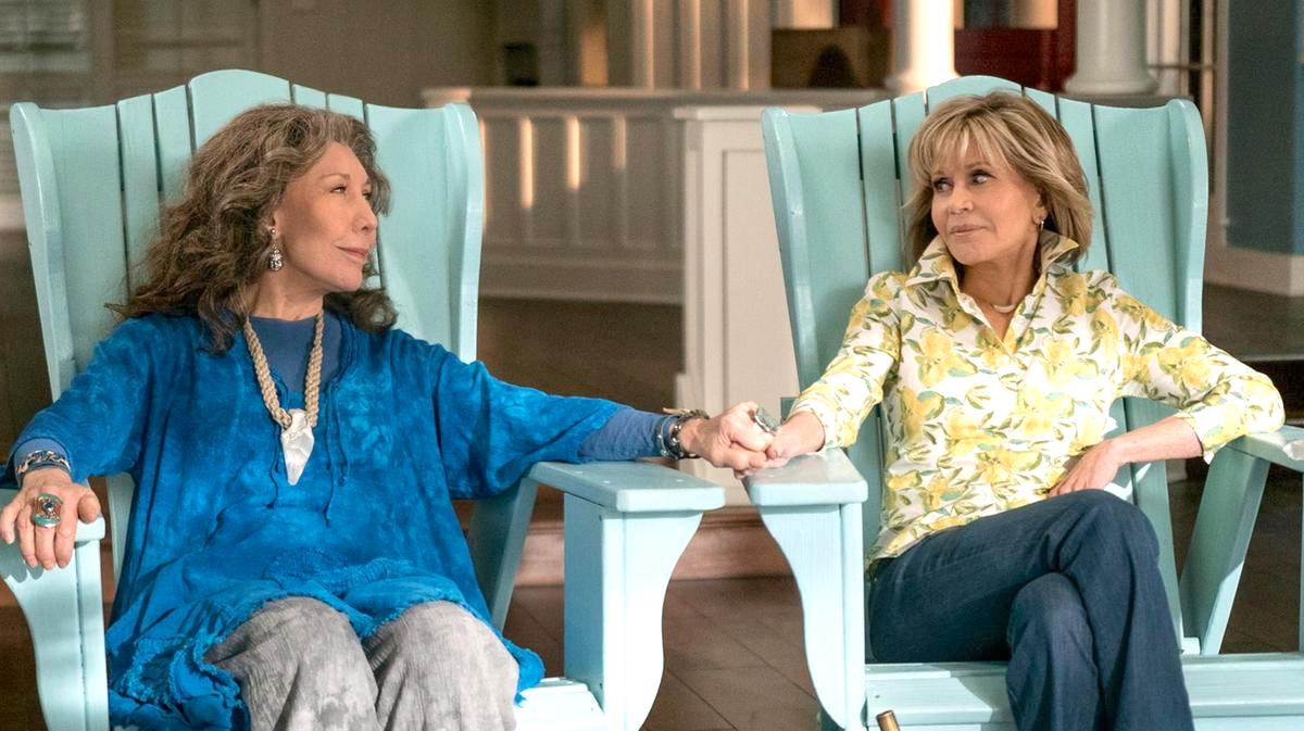 Lily Tomlin and Jane Fonda as Grace and Frankie in the Netflix original show, holding hands on two blue beach chairs