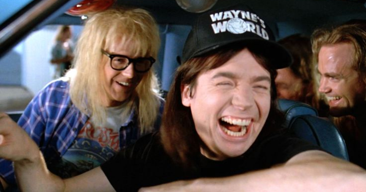 Wayne and Garth laughing while driving in a car together in 'Wayne's World'