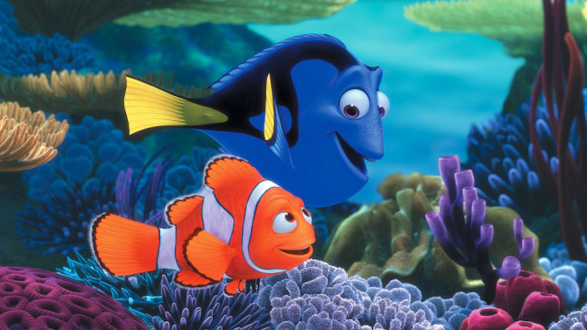 A blue fish, Dory swimming along coral smiling with orange fish, Nemo in a scene from Finding Nemo