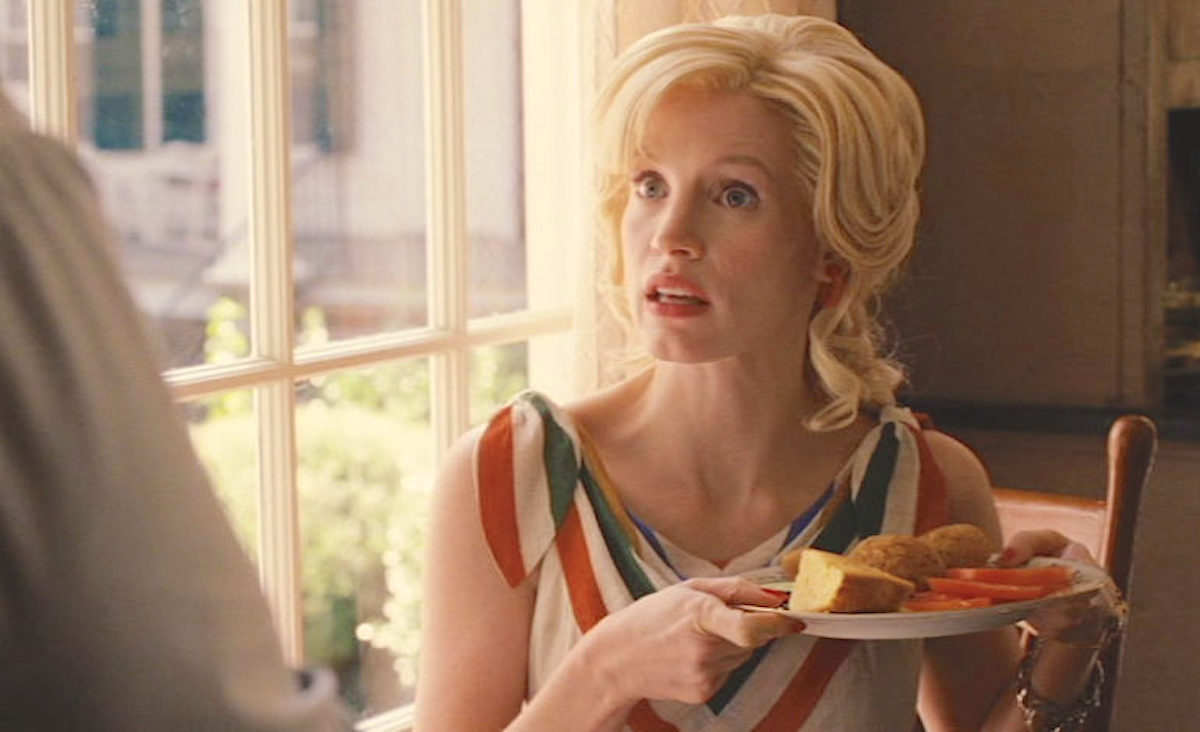 Jessica Chastain in 'The Help' holding a plate of Southern food looking confused