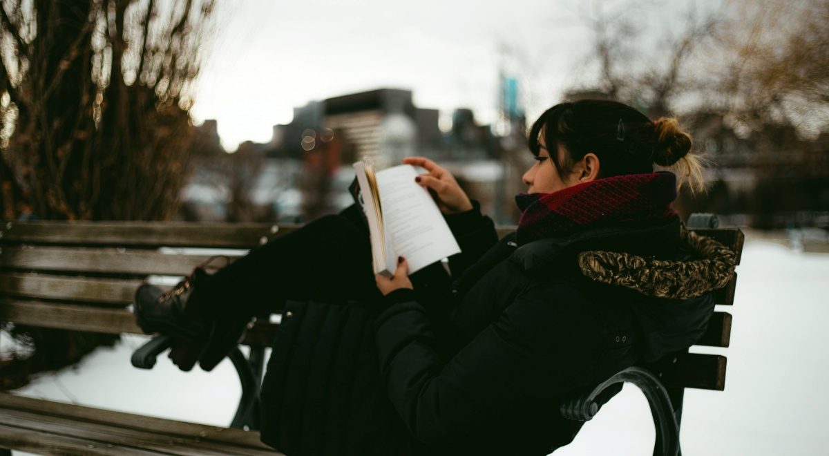 angsty romance novels, image of a pale woman wearing a winter coat reading a book while sitting on a bench, books