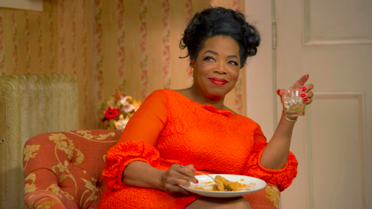 Oprah Winfrey in 'The Butler' sitting on a chair, drinking whiskey and eating, smirking in a red dress