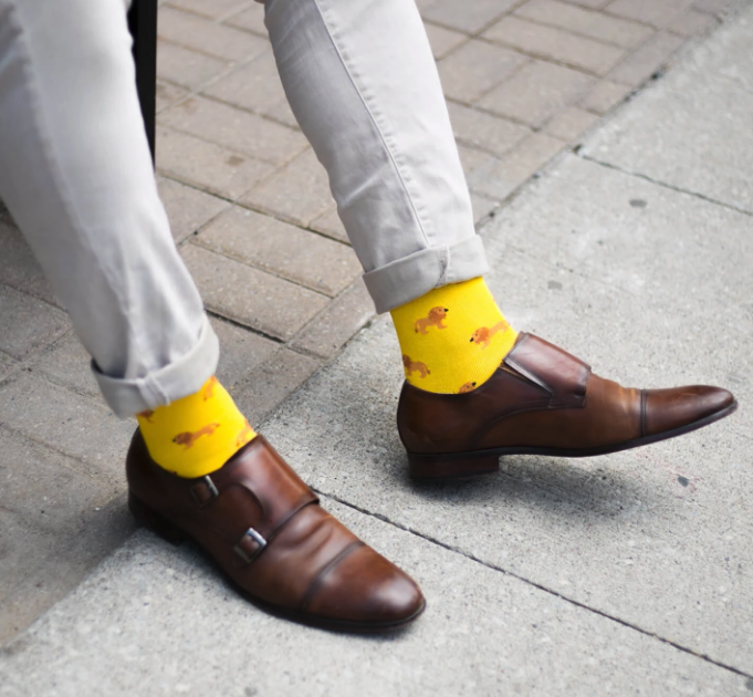 Man wearing bright yellow socks with lions on them for Society Socks