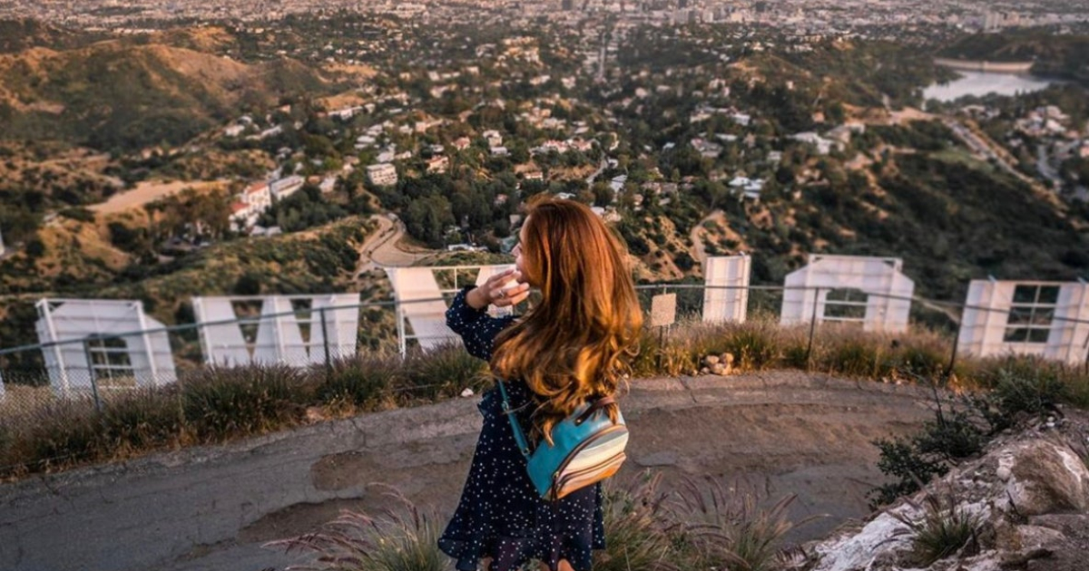 Woman standing behind the Hollywood sign in Los Angeles posing for a photo