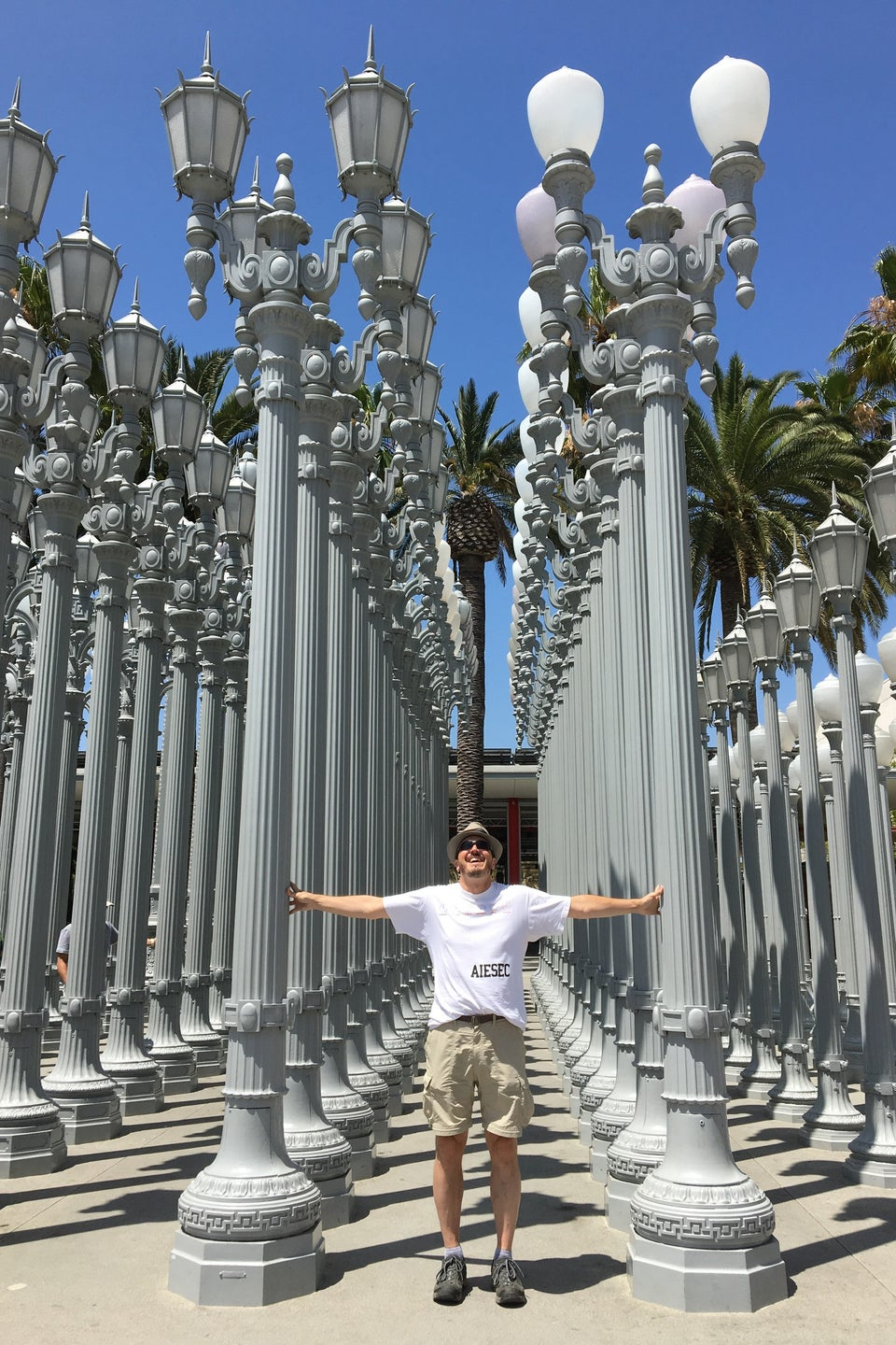 Man standing in front of the lamp posts at LACMA
