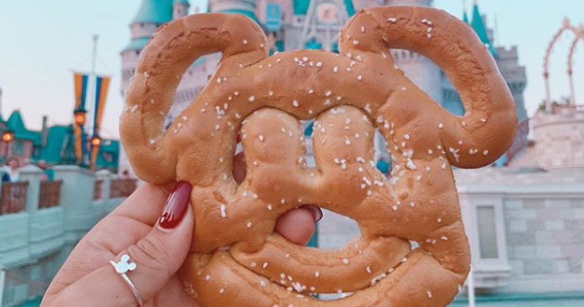 Woman holding a Mickey Mouse pretzel in front of the castle in Disney's Magic Kingdom