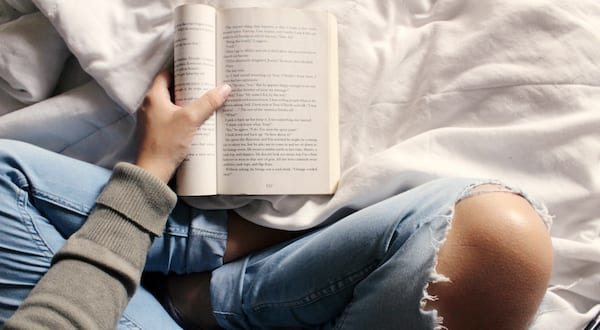 november romance novels, image of a white person sitting cross-legged and reading a book, books