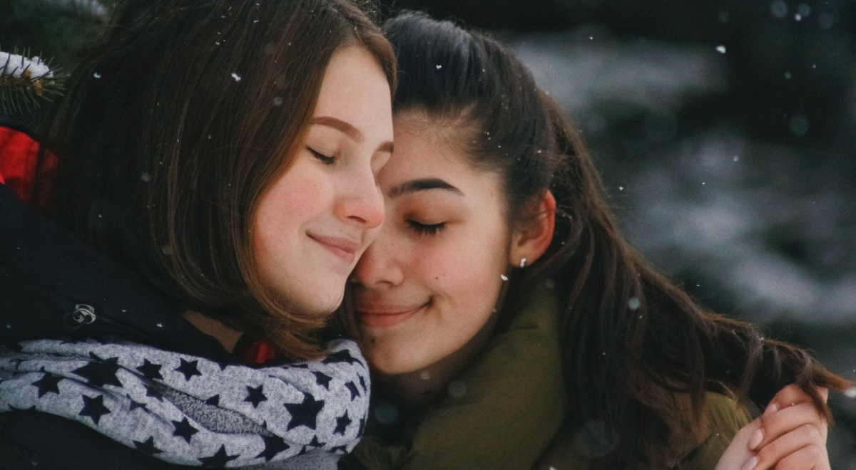 queer christmas books, image of two women wearing coats and cuddling outside, books