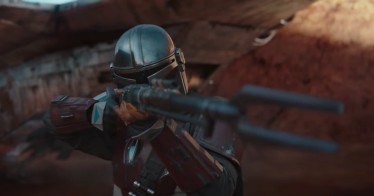 The Mandalorian aiming his weapon at something in the trailer for 'The Mandalorian' on Disney+