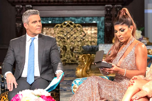 Andy Cohen looking on as Teresa Guidice opens up a gift given to her by her cast mate on a reunion episode of Real Housewives of New Jersey