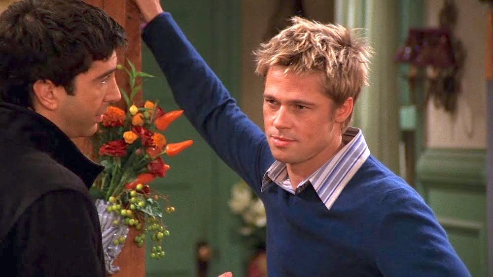 Brad Pitt wearing a blue sweater, talking to Ross, in an episode of Friends glaring at Rachel who is standing off screen