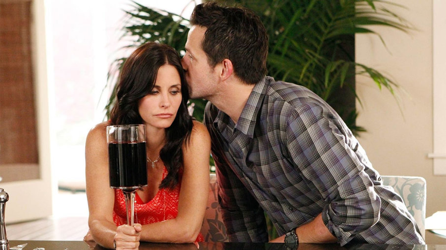 Courtney Cox drinking a huge glass of red wine, being kissed by her boyfriend in a scene from Cougar Town