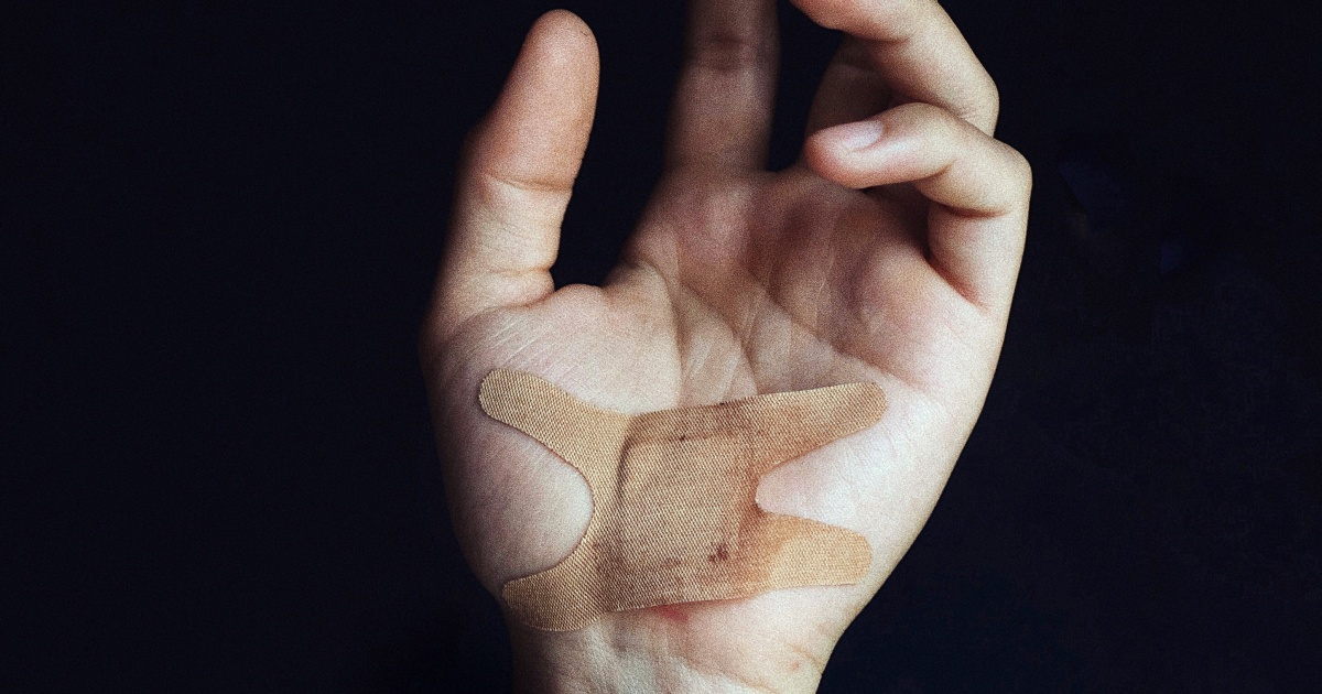 modern love essays, closeup of a person's palm with a bandage on it, books