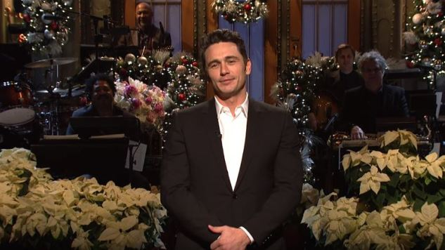 James Franco hosting Saturday Night Live with Christmas decor behind him and white poinsettias