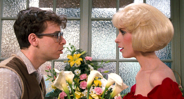 Rick Moranis and Ellen Green looking at each other with flowers behind them in a scene from Little Shop of Horrors