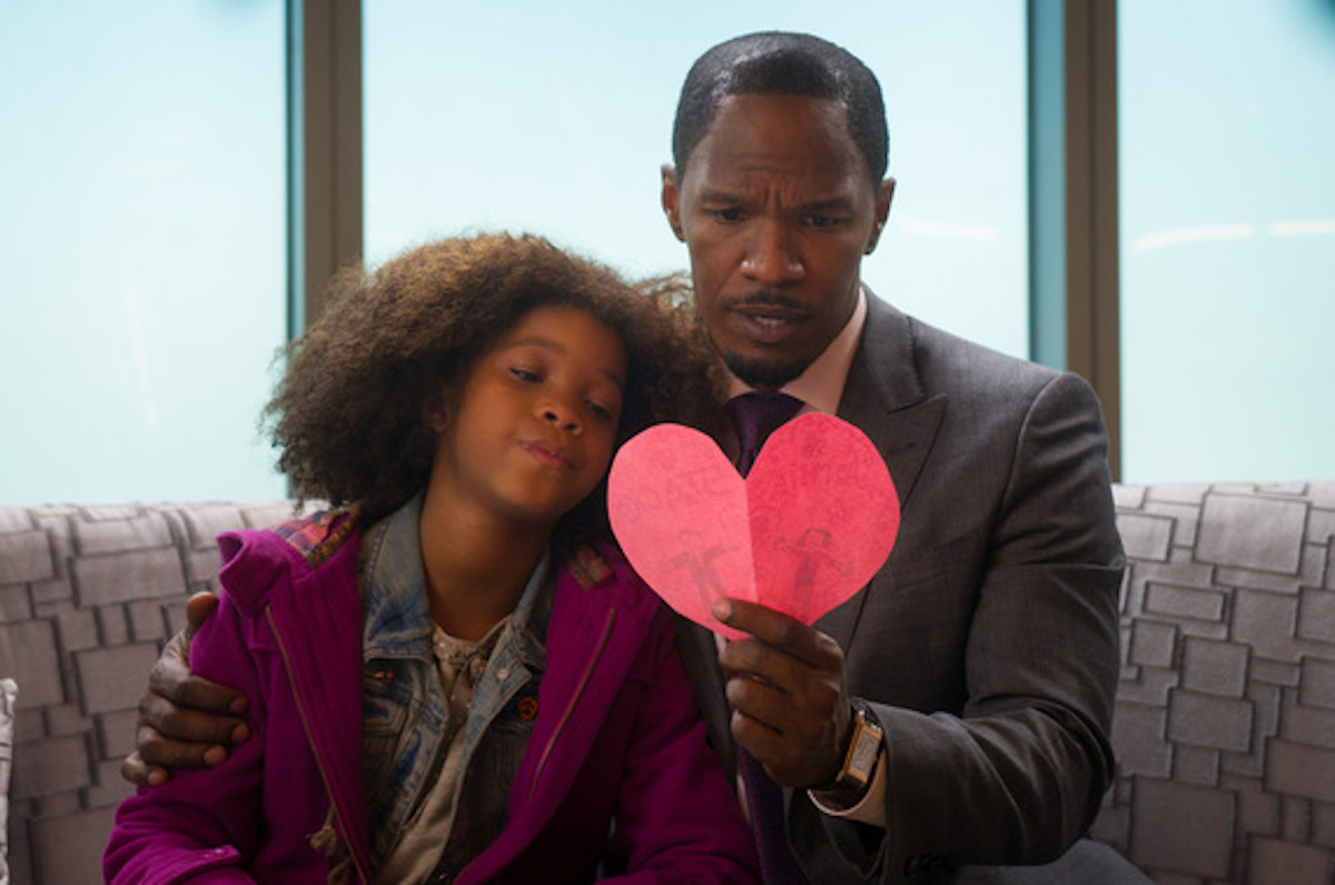 Quvenzhané Wallis and Jamie Foxx in the Annie remake, cuddling and looking at a paper heart together