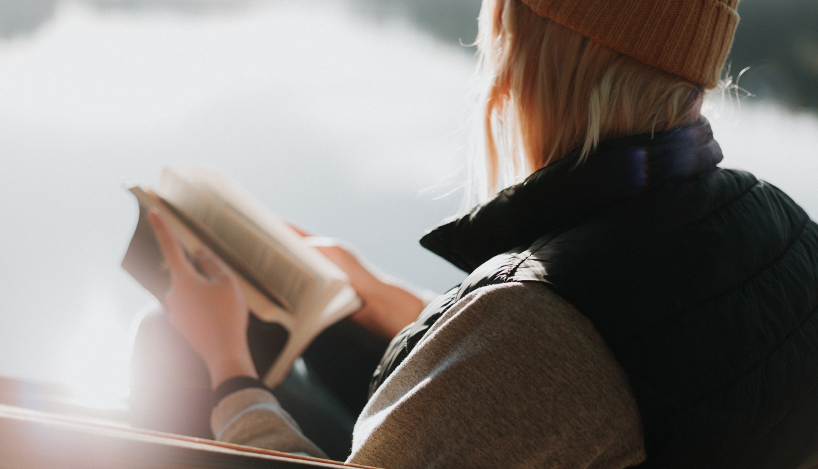 december romance novels, image of a blonde woman wearing a beanie reading a book, books