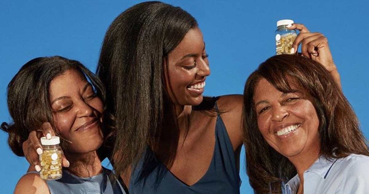Three generations of women posing in front of a blue background with bottles of Ritual vitamins