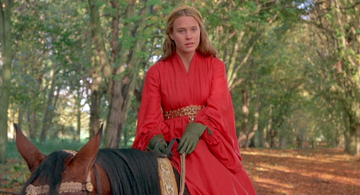 Robin Wright in a red dress, green gloves, wearing a crown riding a horse in the woods in a scene from 'Princess Bride'