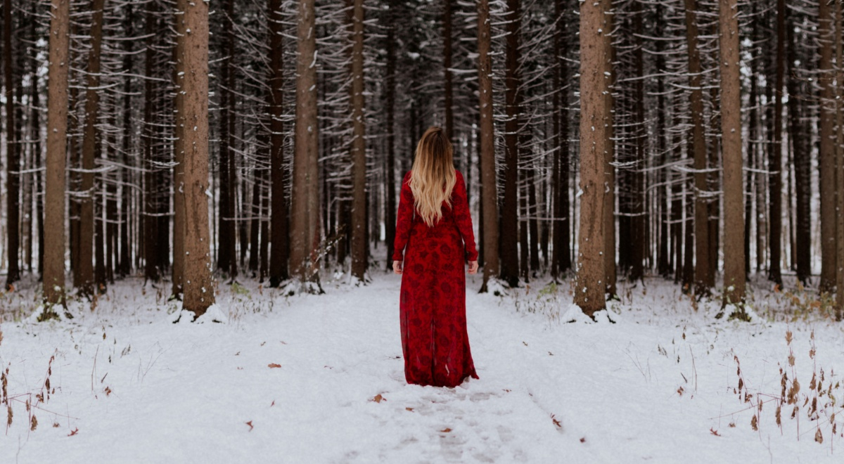 books about yule, image of a white woman in a red dress standing in front of the woods in the snow, books