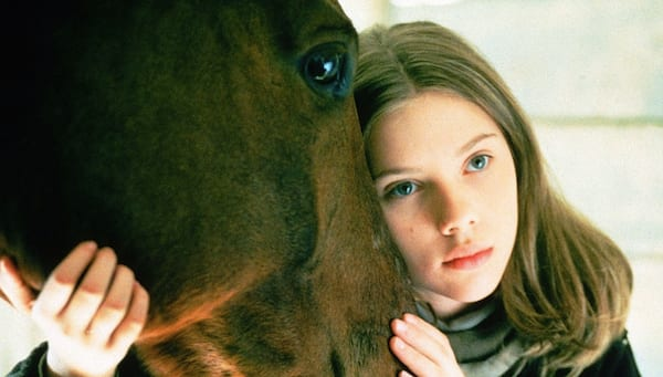 Scarlett Johansson as a young girl with her head on a horses head in a scene from The Horse Whisperer