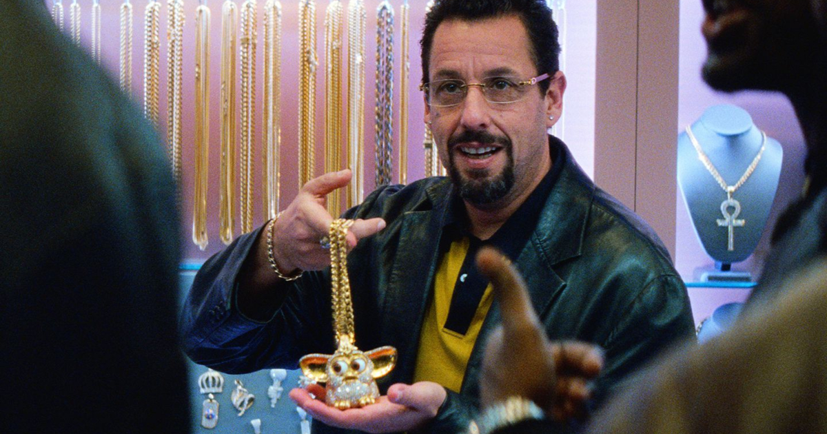 Adam Sandler holding up a Furby gold chain in 'Uncut Gems'