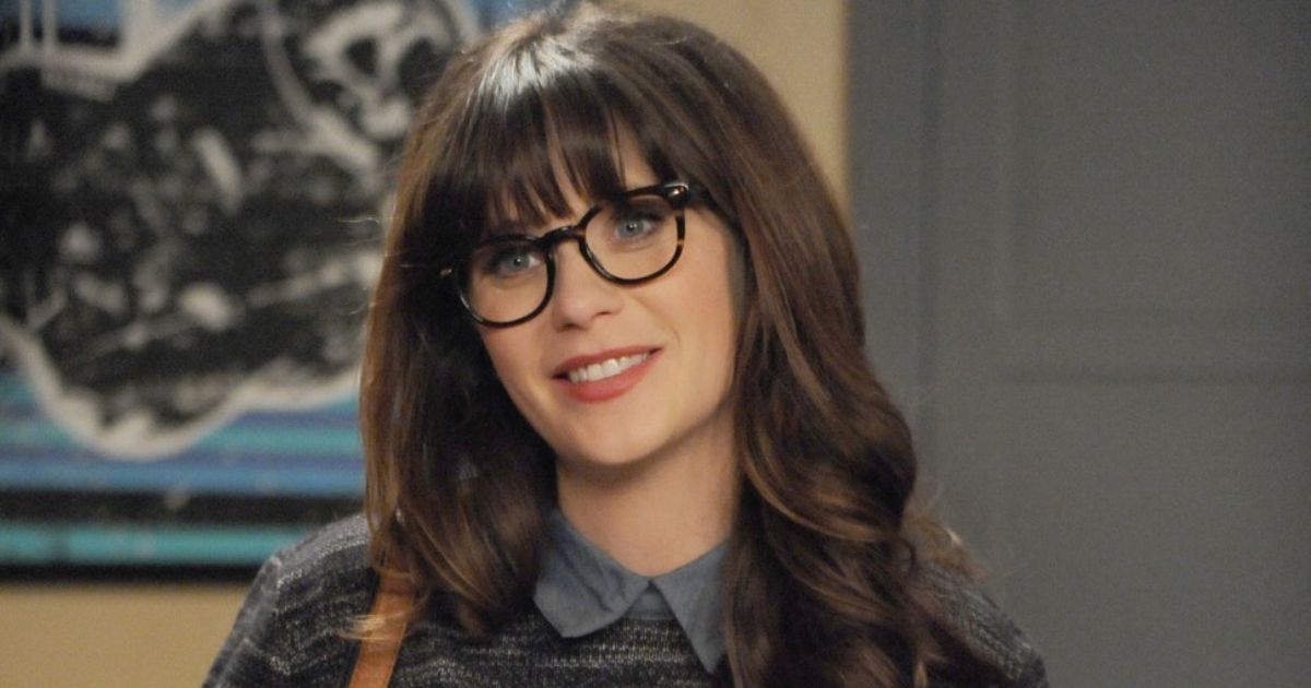 Jess smiling at someone off-camera in a scene from 'New Girl'